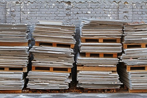 Asbestos cement sheets on pallets on the background of a brick fence