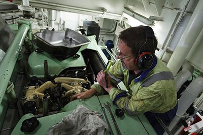 Man working on a ship's engine