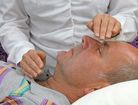 A man receiving reiki energy therapy