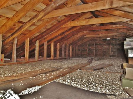 An attic built with black spruce wood was photographed in Ontario, Canada. Vermiculite insulation and stored boxes show in the image.
